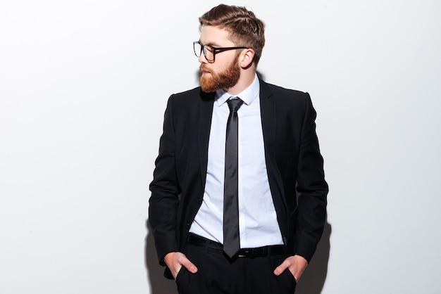 Крутой бородатый деловой человек в очках и черном костюме стоит с руками в карманах и смотрит в сторону.