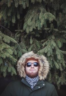 モミの木に対して冬のジャケットを着たクールなひげを生やした男。テキスト用のスペース