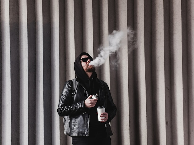 Cool bearded man smokes e-cigarettes and holds a takeaway coffee