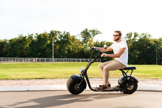 Cool bearded man in sunglasses rides on modern motorbike outdoors
