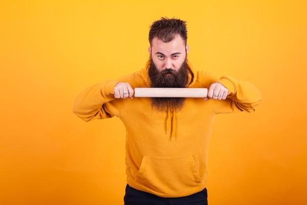 Прохладный бородатый мужчина с помощью кухонного весла и глядя в камеру на желтом фоне. кухонное оборудование.