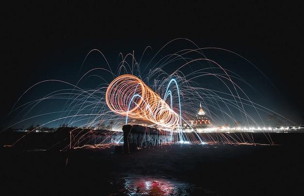 湖の上で夜にクールで美しい息をのむようなスピニングライトショー