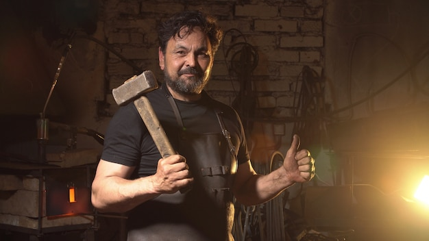 Cool blacksmith portrait with beard in workshop