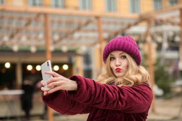キエフの花輪の背景でselfieを作る暖かい服を着たクールなブロンドの女性