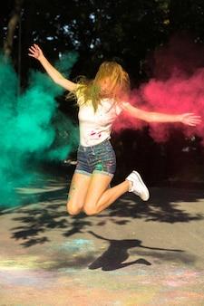 彼女の周りに爆発する鮮やかな色でジャンプするクールなブロンドの女性