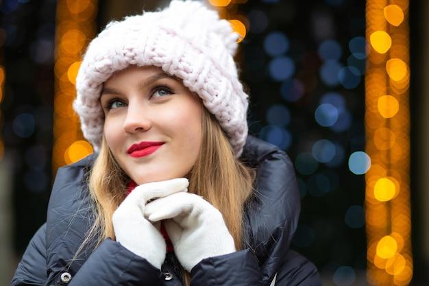 ボケと花輪の背景の上の通りでポーズをとってニット帽をかぶった赤い口紅のクールなブロンドの女性