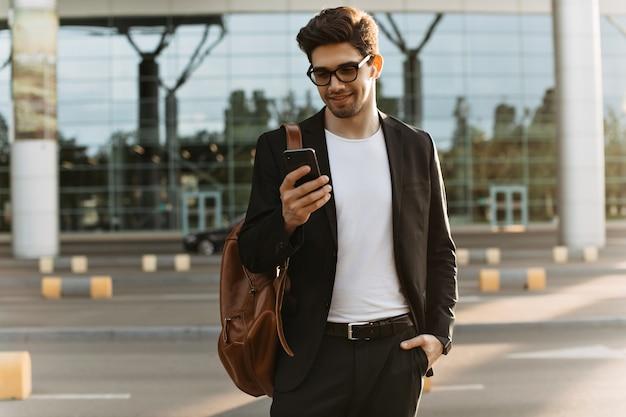 Uomo brunetta cool in chat di occhiali da vista al telefono
