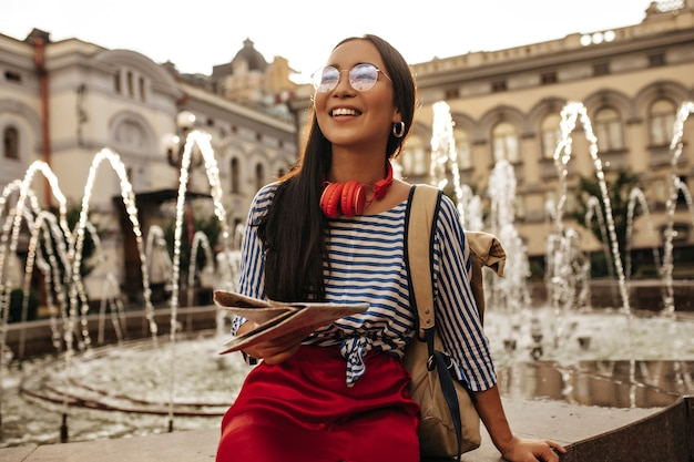 Cool brunette woman in striped shirt, red skirt, headphones and eyeglasses smiles, sits near fountain and holds map