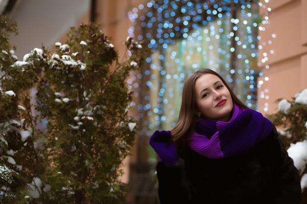 明るい化粧、毛皮のコートを着て、ボケの背景にポーズをとってクールなブルネットの女性