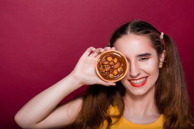 Прохладный брюнетка молодая женщина с красными губами весело с карамельным пирогом. место для текста
