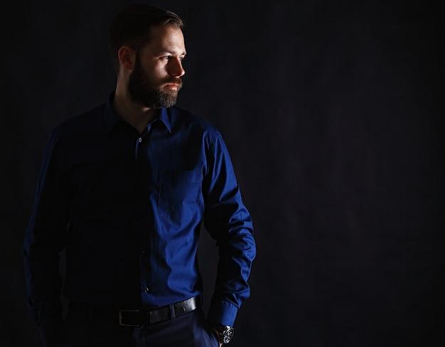 Крутой бизнесмен, стоящий на темной стене градиента