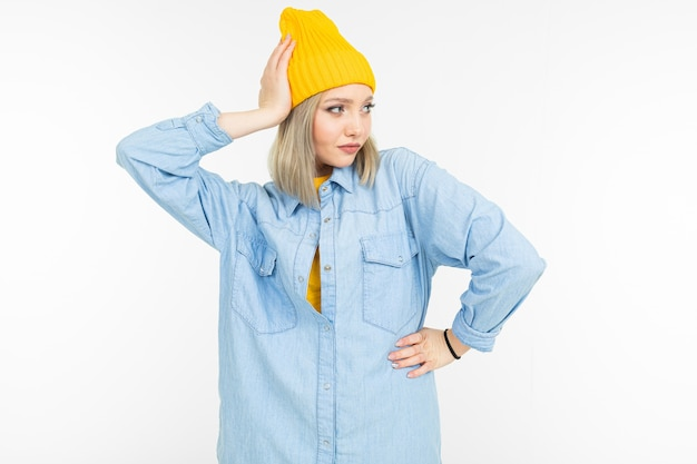 Cool caucasian blond girl in a blue shirt and yellow sweater posing on a white background