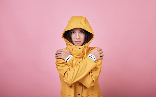 Cool charming sad woman raincoat with dressed hood is frozen and trembling