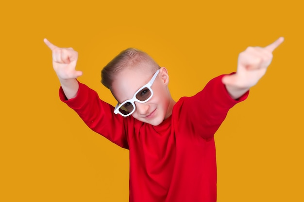 A cool and cheerful child in red clothes and glasses shows hand gestures on a yellow background