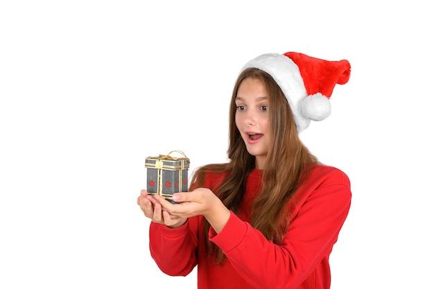 Крутая веселая позитивная оптимистичная красивая женщина в новогодней шапке с рождественским подарком
