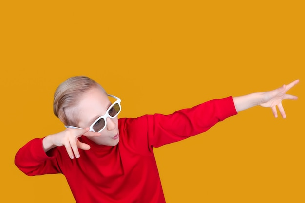 A cool child on a yellow background and in children's 3d glasses shows the direction to the side with his hands