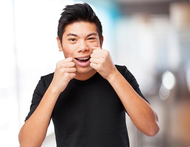 Cool chinese man using dental flosh
