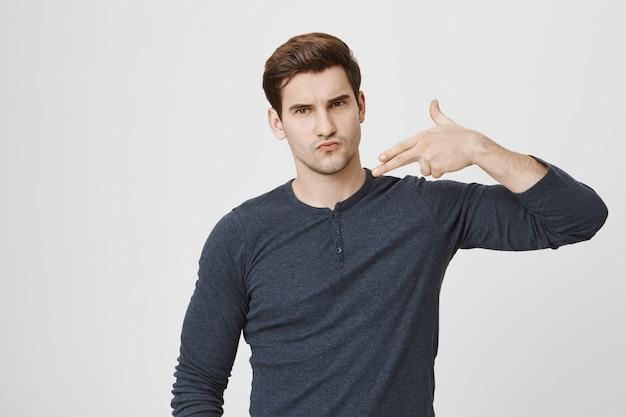 Cool confident guy showing gun gesture