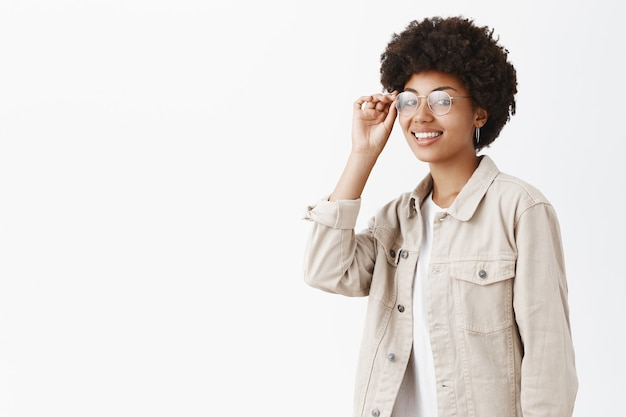 Cool confident and stylish boyish woman with afro hairstyle touching rim of glasses on eyes and smiling broadly being self-assured and ready to challenge new working day