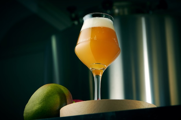 Прохладное крафтовое пиво из пшеницы и манго в классическом бокале с закусками