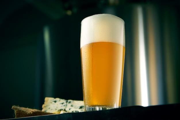 Прохладное крафтовое пшеничное пиво в классическом бокале с закусками