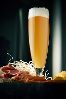 Холодное крафтовое пшеничное пиво в длинном бокале с закусками