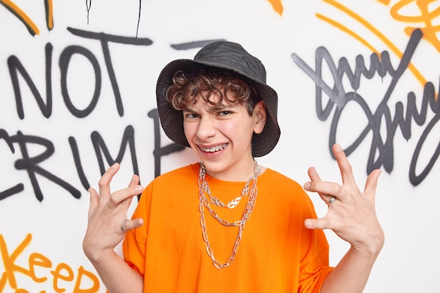 Cool curly hipster guy gestures actively wears hat and orange t shirt belongs to teen subculture poses against graffiti wall