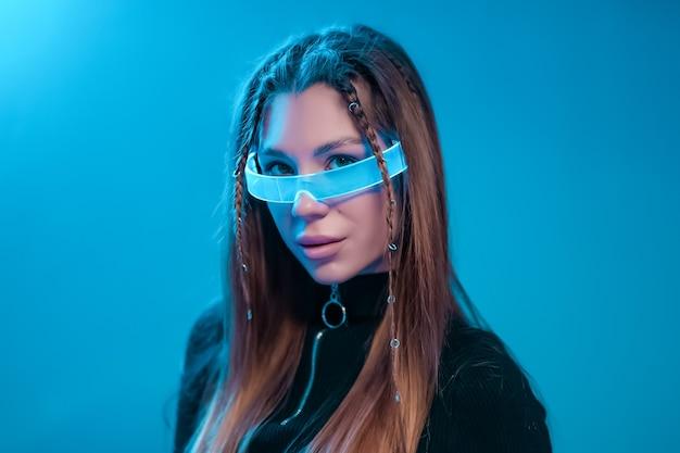 若い女性のクールなサイバーパンクの肖像画。未来的なネオンメガネの女性。