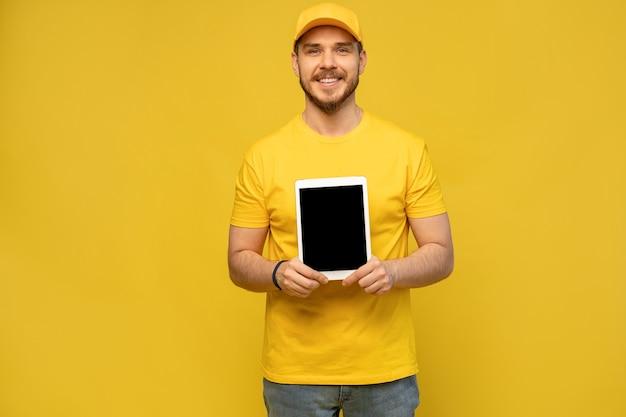 タブレットでクールな配達人。タブレットを示します。カメラを見てください。黄色の壁に分離