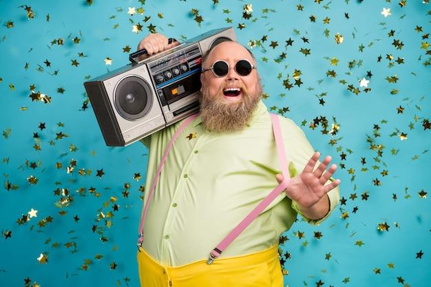 멋진 뚱뚱한 남자는 떨어지는 색종이와 파란색 배경 위에 어깨 당겨 멜빵에 붐 박스를 개최
