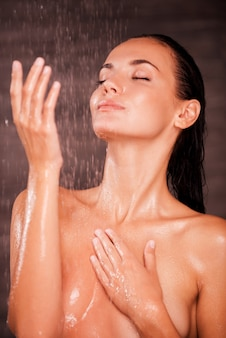 Cool and fresh. beautiful young shirtless woman standing in shower and covering breasts with hands