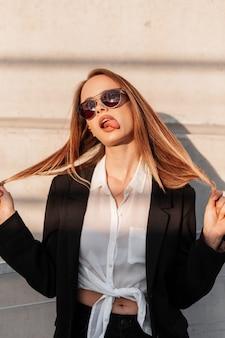 黒のスタイリッシュなブレザーのファッショナブルなサングラスでクールな面白い若い女性は、手に髪を保持し、日没時にヴィンテージの壁の近くに舌を示しています。魅力的な女の子はしかめっ面をします。新作コレクションのファッションウェア。