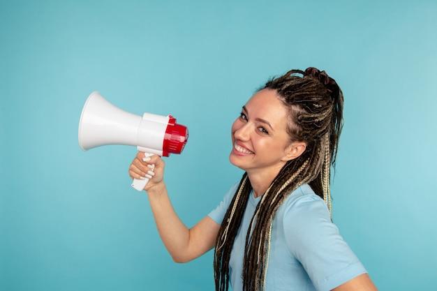 멋진 재미있는 젊은 여자는 파란색 벽 위에 절연 확성기에서 말한다.