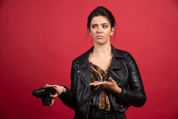 Bella ragazza in giacca di pelle nera che tiene la sua macchina fotografica professionale e sembra insoddisfatta della sua storia fotografica.