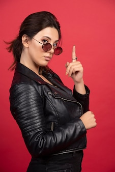 Cool girl in black leather jacket makes attention sign.
