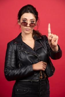 Cool ragazza in giacca di pelle nera fa segno di attenzione.