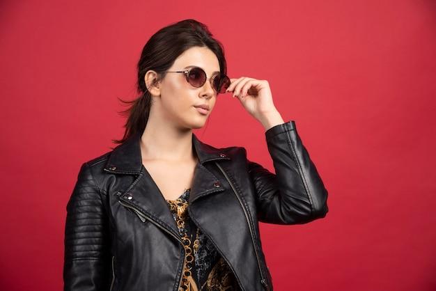 Bella ragazza in giacca di pelle nera in posa in occhiali da sole neri.