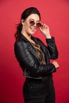 Bella ragazza in giacca di pelle nera e occhiali da sole sembra positiva.