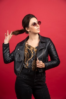 Cool girl in black leather jacket and sunglasses looks strict and demanding.