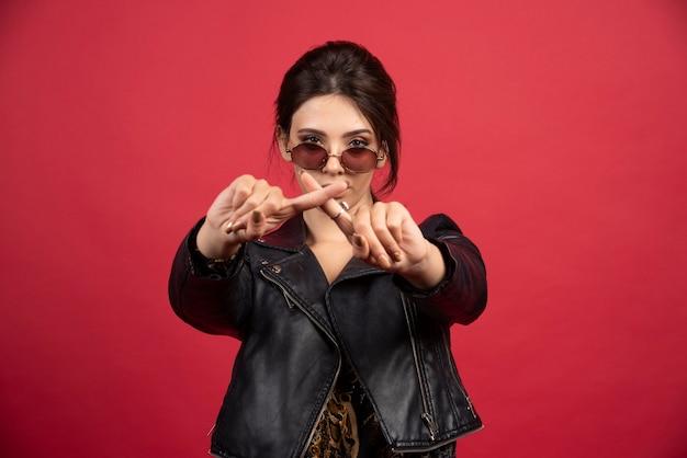 Крутая девушка в черной кожаной куртке скрещивает руки или пальцы, чтобы что-то остановить.