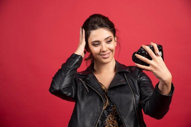 그녀의 전문 카메라를 들고 그녀의 셀카를 찍는 검은 가죽 재킷에 멋진 소녀.
