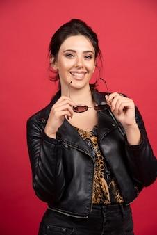 그녀의 선글라스를 꺼내 웃 고 검은 가죽 재킷에 멋진 여자.