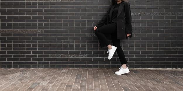 街のレンガの壁の近くに片足で立っている黒いハンドバッグとトレンディなジャケットの革のスタイリッシュなスニーカーのファッションデニムパンツのクールな女の子。クローズアップの女性の体。ファッショナブルなカジュアルな若者の女性が着る