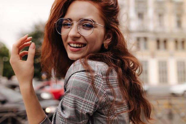 Крутая девушка в клетчатом наряде и очках улыбается
