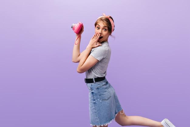 멋진 소녀는 놀란 모습과 핑크색 카메라로 포즈를 취합니다. 데님 스커트와 회색 셔츠 점프에 머리 띠와 매력적인 젊은 여자.