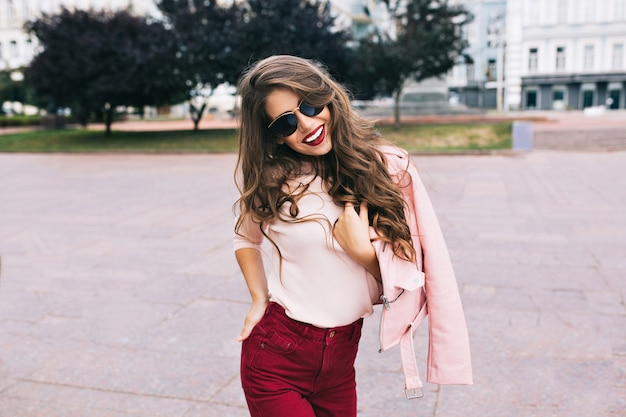Cool girl in marsala pants with long hairstyle is posing in city. she wears sunglasses, smiling .