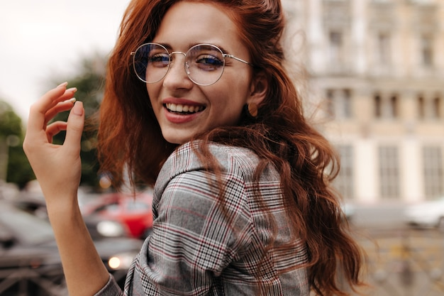 Cool girl in plaid outfit and eyeglasses smiling