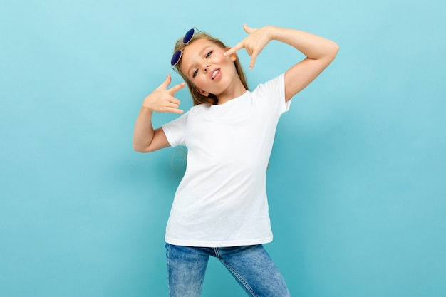 Cool girl in a white t-shirt with mockup on light blue