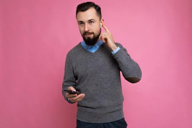 Крутой симпатичный брюнет небритый молодой человек с бородой в сером и синем свитере