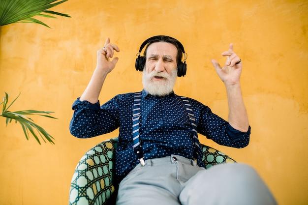 멋진 수염을 가진 멋진 잘 생긴 노인, 의자에 앉아 이어폰에서 좋아하는 음악을 즐기십시오. 노란색 배경에 절연